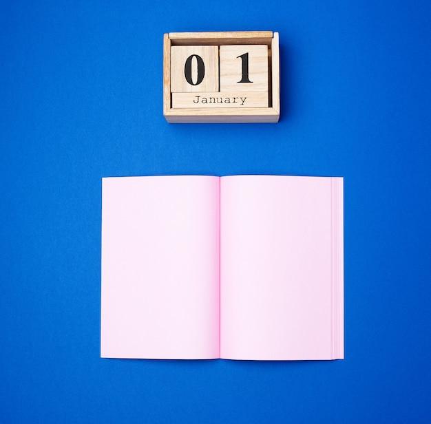 Calendario retrò in legno con la data del 1 gennaio e un quaderno aperto con fogli rosa vuoti