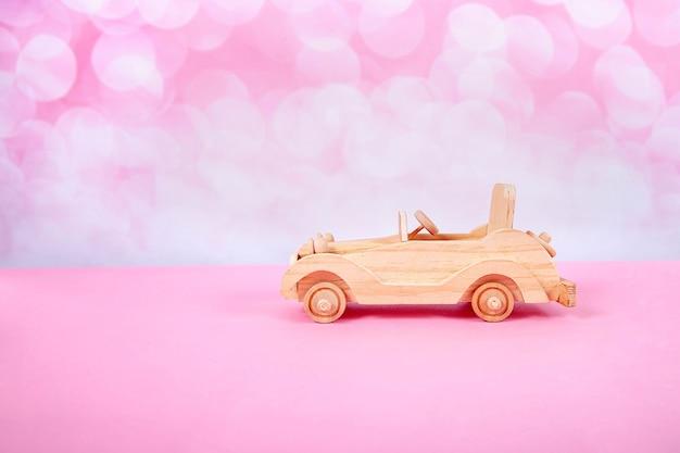 Giocattolo auto retrò in legno su uno sfondo rosa con bokeh