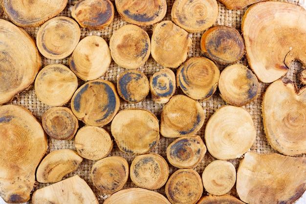 Anelli di legno sul primo piano della tela da imballaggio. sfondo di legno naturale