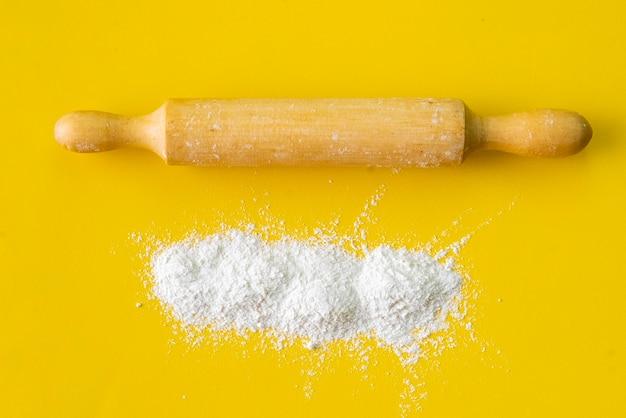 Mattarello in legno e farina di grano bianco sul tavolo, attrezzatura e ingredienti per le cotture