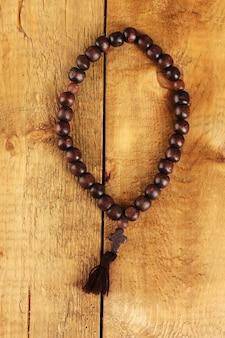 Il rosario di legno borda sul primo piano della tavola di legno