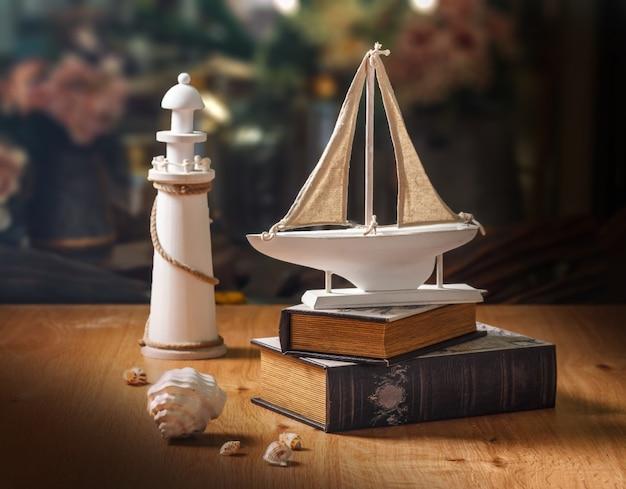 Modello di barca a vela in legno su libri, faro e conchiglie bianche, stile vintage