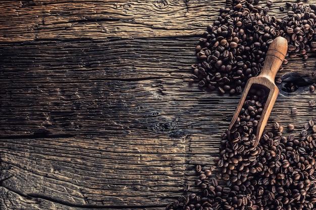 Paletta di legno piena di chicchi di caffè sul vecchio tavolo di quercia.
