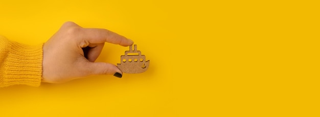 Nave di legno in mano su sfondo giallo, viaggio o concetto di vacanza estiva, mock-up panoramico
