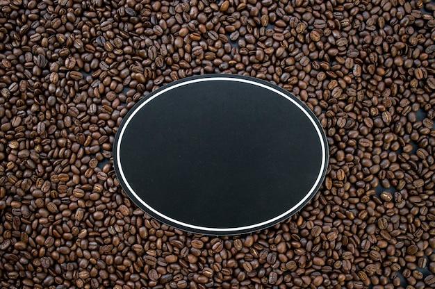 Caffè caldo e fagioli del segno di legno sul fondo di legno della tavola
