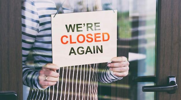 Il cartello in legno con il testo: scusa, siamo di nuovo chiusi appesi alla porta del bar