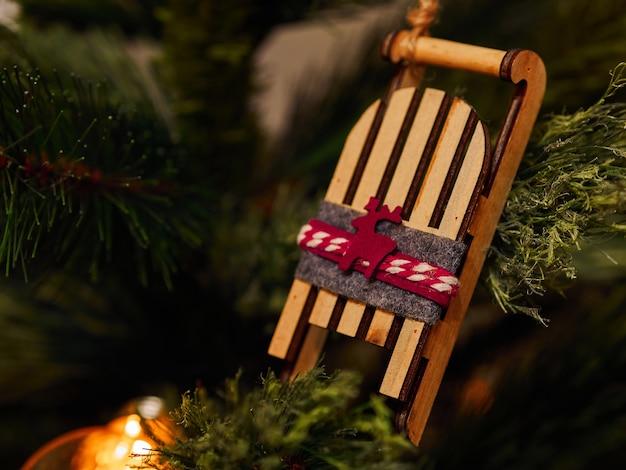 Giocattoli di natale con la slitta in legno e torce elettriche sull'albero di natale