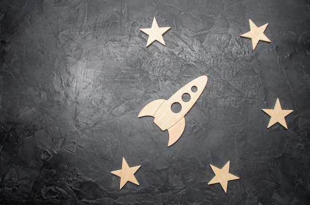 Razzo spaziale in legno e stelle su uno sfondo scuro. educazione e scienza popolare.