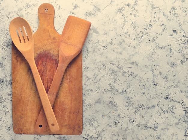 Una spatola e un cucchiaio di legno per friggere sulle pentole, un bordo per cucinare su una superficie di calcestruzzo bianca