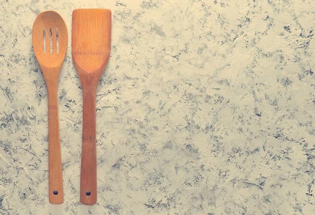 Una spatola di legno e un cucchiaio per friggere su padelle su una superficie di cemento bianco