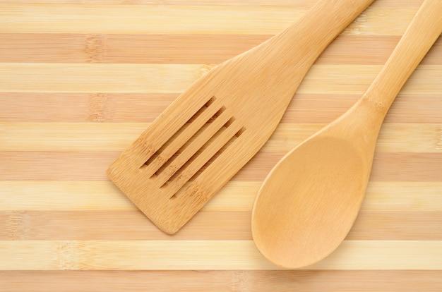 Spatola e cucchiaio di legno isolati sul tagliere