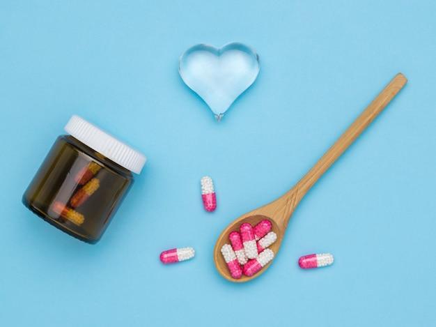 Un cucchiaio di legno e una bottiglia di capsule medicinali e un cuore di vetro