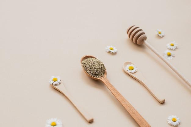 Un cucchiaio di legno e camomille su una superficie beige, il concetto di una sana alimentazione, vista dall'alto Foto Premium