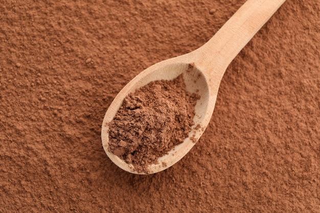 Cucchiaio di legno e cacao in polvere, fine alta e spazio della copia