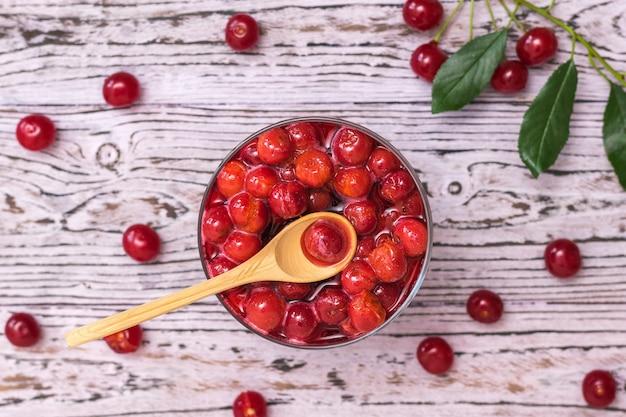 Cucchiaio di legno in una tazza di marmellata di ciliegie su un tavolo di legno