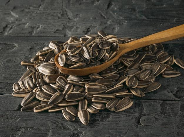 Cucchiaio di legno in un mucchio di semi di girasole su un tavolo di legno scuro. la fresca resa del girasole.
