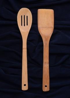 Cucchiaio di legno e una spatola su sfondo nero. vista dall'alto.