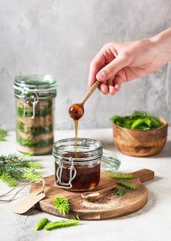 Cucchiaio di legno con miele fatto in casa che scorre a base di giovani punte di abete verde e zucchero naturale