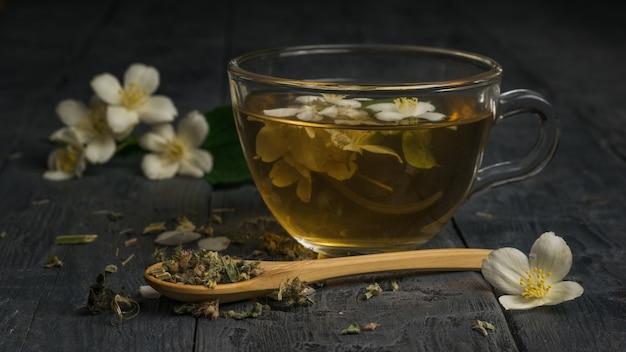 Un cucchiaio di legno con tè verde e una tazza di tè al gelsomino. una bevanda tonificante che fa bene alla salute.