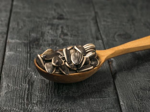 Cucchiaio di legno con grandi semi di girasole su un tavolo di legno. la fresca resa del girasole.