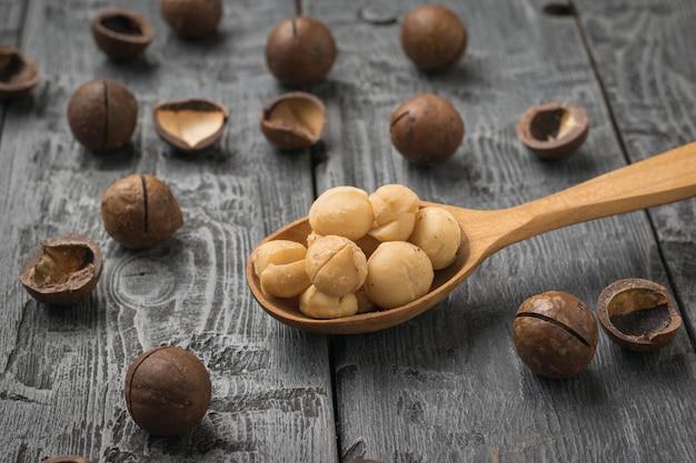 Cucchiaio di legno con noci di macadamia sbucciate e non sbucciate su un tavolo di legno. superfood.