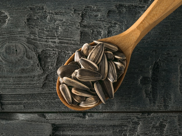 Cucchiaio di legno con semi di girasole su un tavolo di legno nero. la fresca resa del girasole.