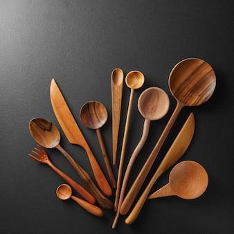 Cucchiai di legno e coltello su sfondo nero