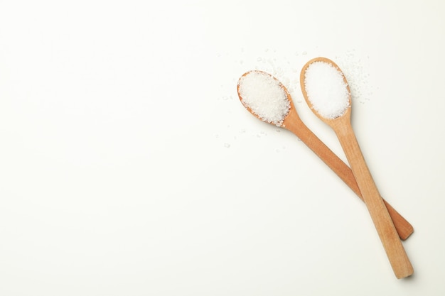 Cucchiai di legno con sale su bianco