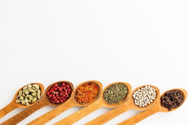 Cucchiai di legno con varietà di spezie con copia-spazio