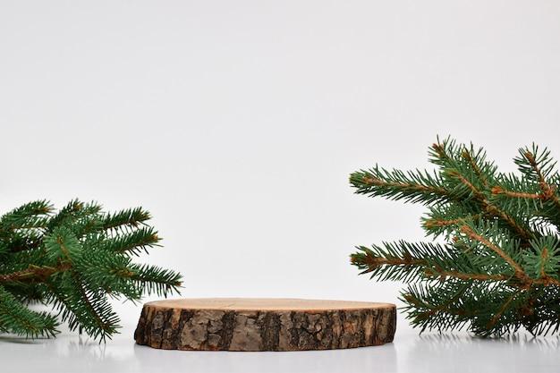 Un palco in legno con un ramo di abete su sfondo bianco. un podio per la presentazione di merci e cosmetici.