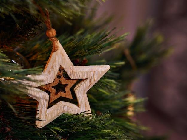 Giocattoli di natale stella in legno e torce elettriche sull'albero di natale
