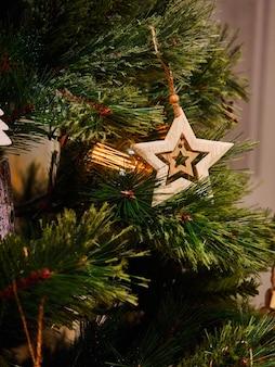 Giocattoli di legno della stella e torce elettriche sull'albero di natale