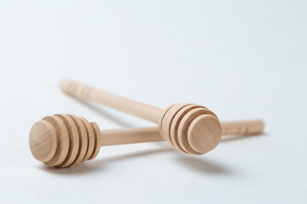 Bastoncini di legno per miele su sfondo bianco