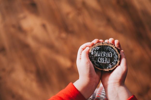 Ceppo di legno nelle mani dei bambini con le parole, buon natale
