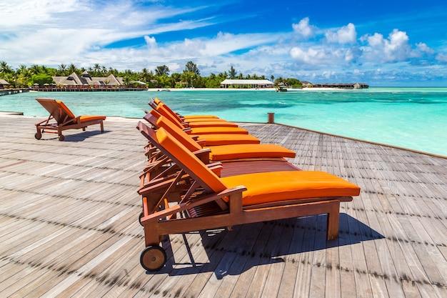 Lettino in legno sulla spiaggia tropicale delle maldive