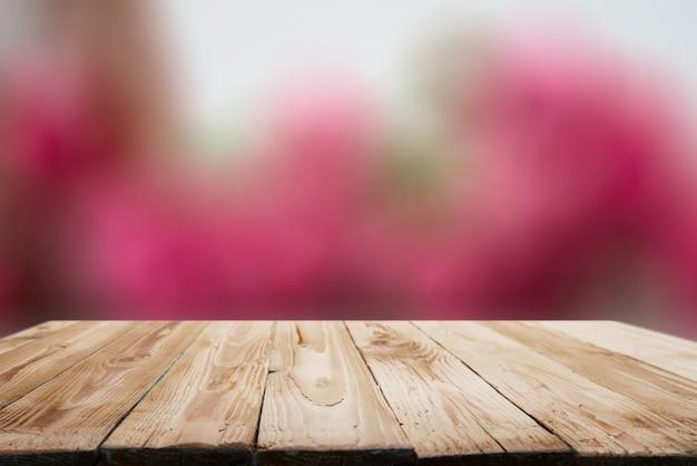 Superficie in legno su sfondo bianco e rosa sfocato