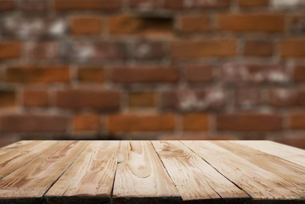 Superficie in legno su sfondo sfocato muro di mattoni