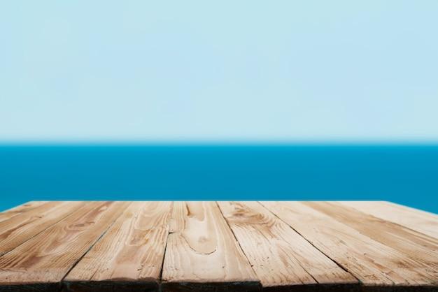 Superficie in legno su sfondo bokeh di mare blu durante il giorno