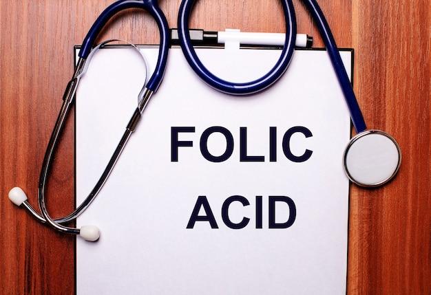 Su una superficie di legno giace uno stetoscopio e un foglio di carta con la scritta acido folico. lay piatto