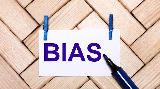 Su una superficie di legno, una carta bianca con il testo bias su mollette blu e un pennarello blu