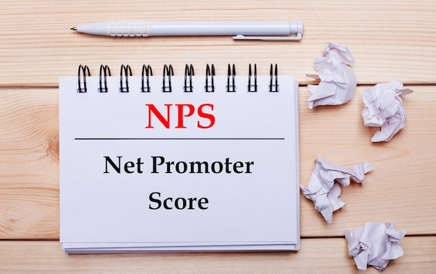 Su una superficie di legno, un taccuino bianco con la scritta nps net promoter score, una penna bianca e fogli di carta bianca sgualciti