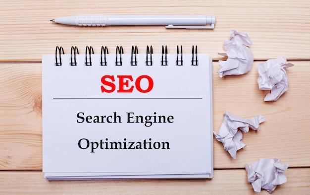 Su una superficie di legno, un taccuino bianco con la scritta seo search engine optimization, una penna bianca e fogli di carta bianca stropicciata