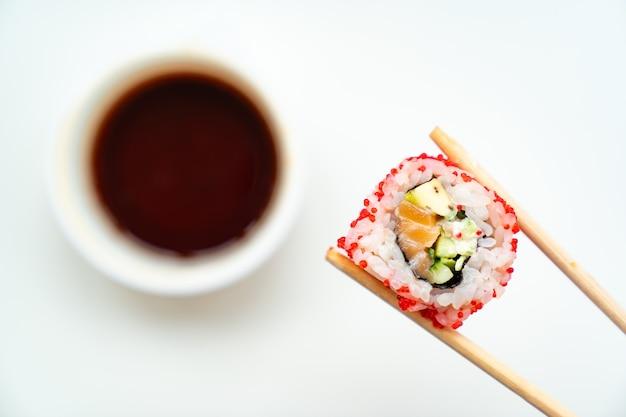 I bastoncini di sushi in legno continuano a rotolare con caviale rosso, pesce, riso e avocado con una tazza di salsa di soia su uno sfondo bianco. ordina cibo con consegna online. cucina giapponese.