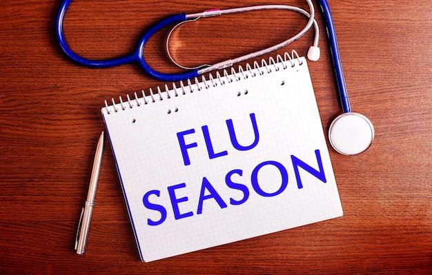 Su un tavolo di legno ci sono una penna, uno stetoscopio e un taccuino con l'etichetta flu season