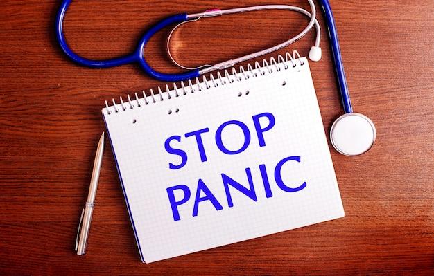 Su un tavolo di legno ci sono una penna, uno stetoscopio e un taccuino con l'etichetta stop panic