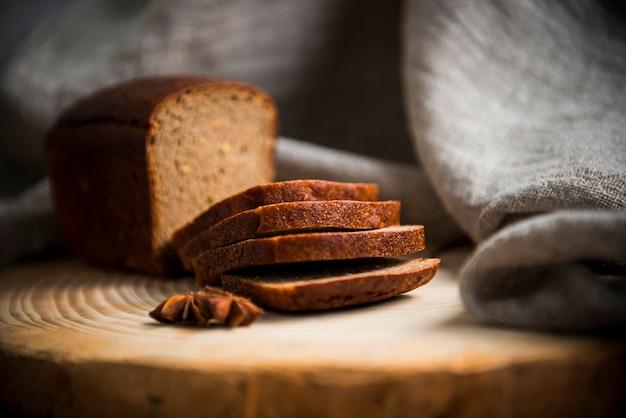 Su un tavolo di legno ci sono fette di pane nero a fette su uno sfondo sfocato