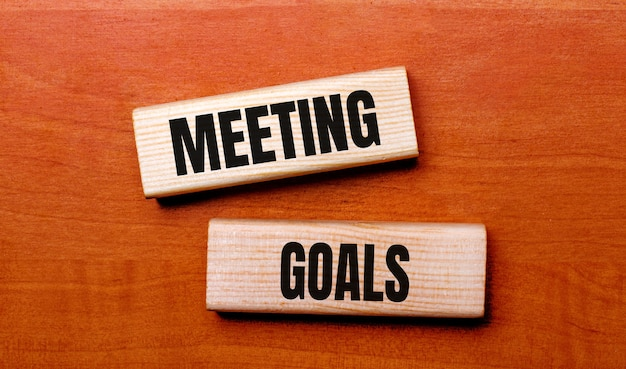 Su un tavolo di legno ci sono due blocchi di legno con la domanda di testo obiettivi dell'incontro