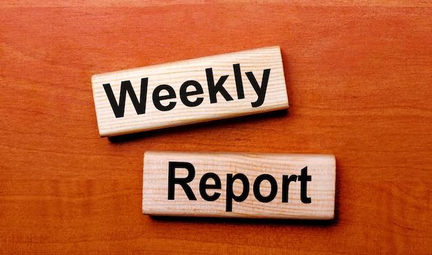 Su un tavolo di legno ci sono due blocchi di legno con la domanda di testo rapporto settimanale
