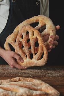 Sul tavolo di legno e il fornaio mantiene il pane fougas appena sfornato