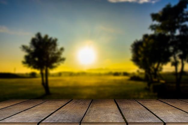 Tavolo in legno e sfocatura di bellezza in una giornata di sole sul campo di riso con cielo e montagne come sfondo.